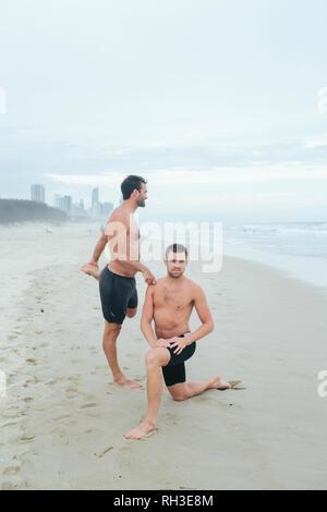 Men stretching on beach - Stock Image