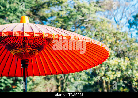 Japanese traditional red umbrella or parasol with green trees - Stock Image