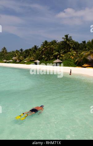 Maldives snorkeling - a tourist snorkelling off the beach, Veligandu Island, Rasdhoo atoll, the Maldives Asia - Stock Image