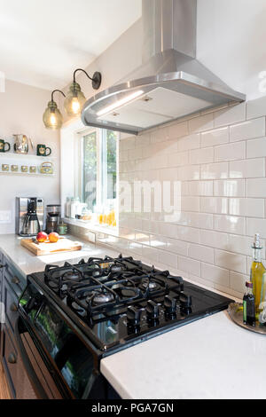 A gas stove in a modern home kitchen with an electric ventilation hood with a white tile backsplash - Stock Image