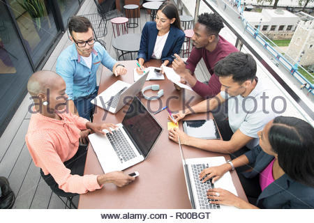 Businesspeople with laptops during meeting on balcony - Stock Image