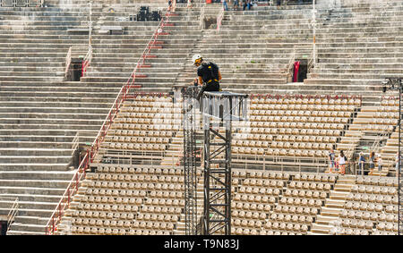 VERONA, ITALY - SEPTEMBER 2018: Specialist rigger on top of a high metal lighting gantry dismantling the frame after a classical concert in Verona Are - Stock Image