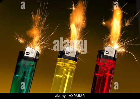 Three lighters shooting flames and sparks. - Stock Image