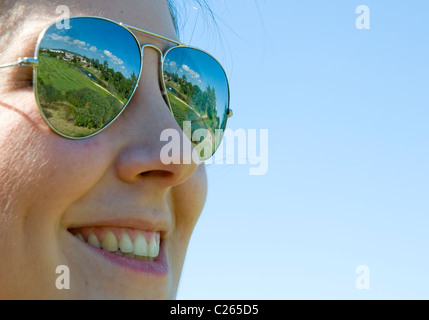 A smiling young woman wearing sunglasses that reflect the layout of an Algarve golf course in the lenses - Stock Image