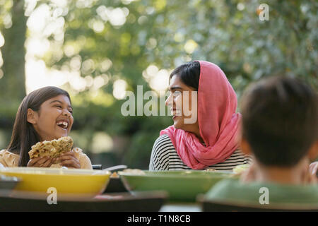 Mother in hijab and daughter laughing at dinner table - Stock Image