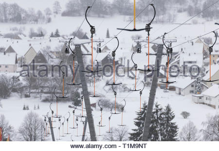 Ski lift cables with ski resort in background, Roemerstein-Donnstetten, Germany - Stock Image