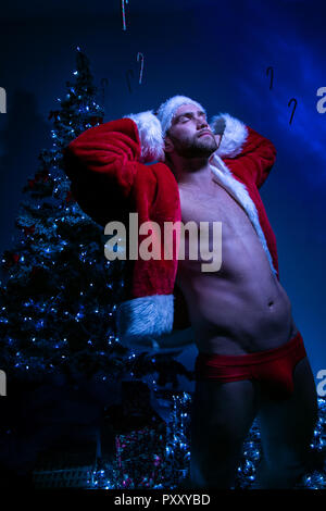Handsome male santa with open jacket and wearing red underwear stretching in front of christmas tree revealing defined body - Stock Image