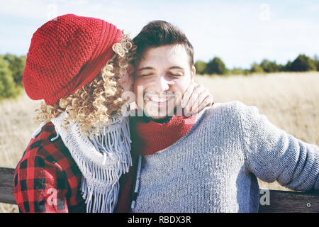 Romantic young couple of a beautiful blonde woman with curly hair and wearing a red wool cap kissing to her boyfriend and a handsome man outdoor - Stock Image