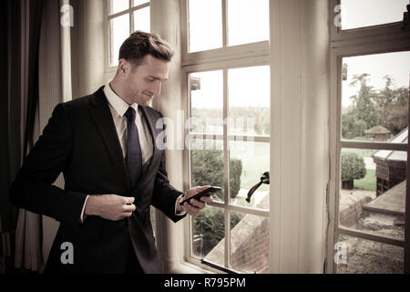 Good looking businessman standing next to large window using mobile phone - Stock Image