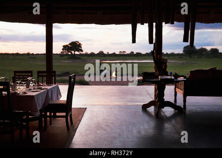 Outdoor restaurant, man on background at campfire - Stock Image