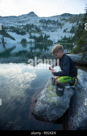 Side view shot of a boy filling a water bottle from a lake, Selkirk Mountains, Sandpoint, Idaho, USA - Stock Image