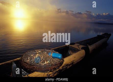 Puçá, gear used for shrimp fishing, canoe in sunrise, quiet sea landscape, morning mist dissipating. Bahia State, Brazil. - Stock Image