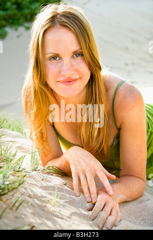 Portrait of pretty redheaded woman lying in sand looking at viewer - Stock Image