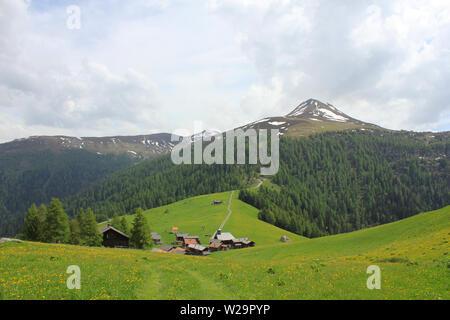 Idyllic village Obermutten in early summer and Muttener Horn, mountain in Switzerland. - Stock Image