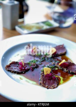 Tuna Sashimi with slices of fried garlic - Stock Image