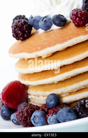Stock image of stack of pancakes with an assortment of berries and whipped cream on top - Stock Image