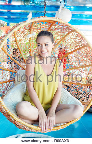 Young woman sitting on hanging spherical chair - Stock Image