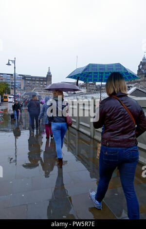 Edinburgh, Scotland, UK. 12th October, 2018. People sheltering under umbrellas on the Edinburgh city centre streets as heavy downpours hit the east coast. Credit: PictureScotland/Alamy Live News - Stock Image