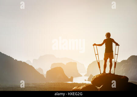 Disabled man with crutches stands on a big rock and looking at great view to islands and mountains. Space for text. - Stock Image