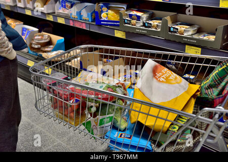 Grocery shopping with trolley in supermarket - Stock Image