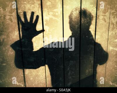 Man casting a shadow on a wall, Expressing, STOP!, no more! - Stock Image