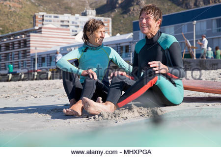 Senior surfing friends sitting on Beach - Stock Image