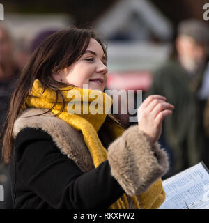 Attractive young lady choirmaster conducting the Wellesbourne Community Choir at the Joseph Arch centenary day outside. - Stock Image