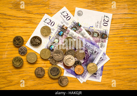 Cash in form of English coins and currency notes on a pine table - Stock Image