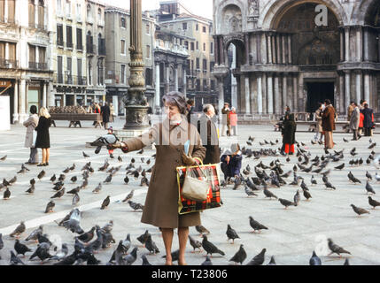 54 Year Old Woman Tourist Feeds the Pigeons , Venice Italy, 1974 - Stock Image