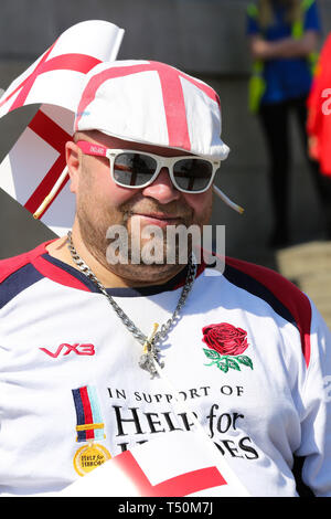 Trafalgar Square. London, UK. 20th Apr, 2019. A man wearing England Flag design sunglasses attends the annual 'Feast of St George' event in Trafalgar Square, to celebrate the Patron Saint of England. St George's Day is on 23 April. Credit: Dinendra Haria/Alamy Live News - Stock Image