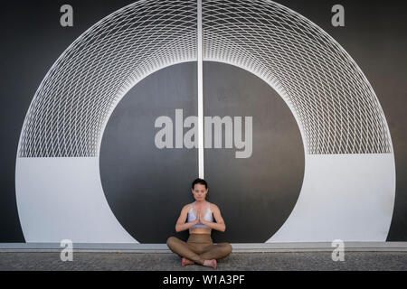 woman meditating and practicing yoga outside in front of a geometric symmetrical pattern on a wall. - Stock Image