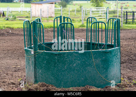 Empty round bale feeder for horses with baler twine wrapped around and sitting in paddock - Stock Image