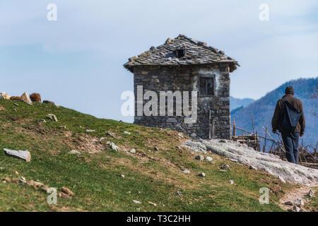 Shepherd in Rhodope mountain, Bulgaria. Old stone house in background - Stock Image