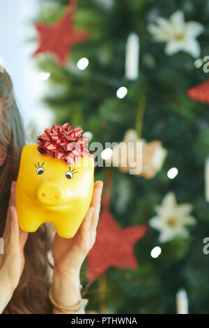 Closeup on smiling young woman in red dress showing yellow piggy bank with red bow near Christmas tree - Stock Image