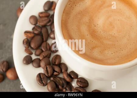 Detail of cup of coffee with perfect cream and coffee beans on gray background - Stock Image