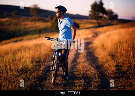 Full length of male cyclist standing with bicycle on dirt road field - Stock Image