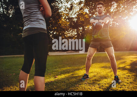 Young man doing kettlebell weight workout with personal female trainer in the park. Fit man swinging kettle bell - Stock Image