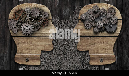 Two wooden heads with gears commucating - Stock Image