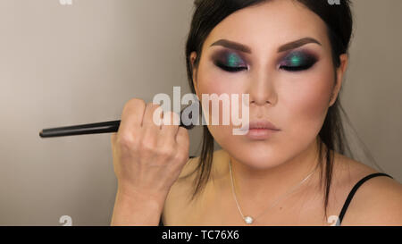 Makeup artist working with Asian model in beauty salon. Face sculpt. Contouring. Make up woman face. Contour and highlight. Copy space, text space. Be - Stock Image
