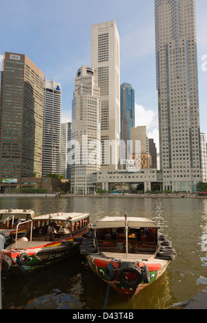 Bum boats docked at the Colonial District and the skyline along the Singapore River beyond, Singapore - Stock Image