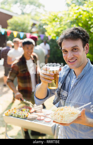 Portrait happy man drinking beer and barbecuing in backyard - Stock Image