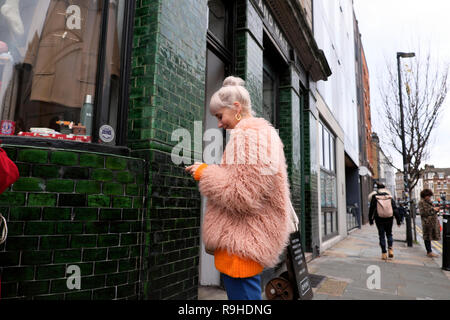 Trendy fashionable young woman shopper in pink fake fur texting outside a shop in Redchurch Street Shoreditch  London  E2 UK   KATHY DEWITT - Stock Image