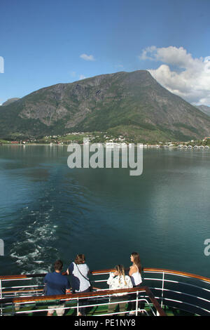 Skjolden, Norway - 6 August 2018: Tourist on a cruise ship as it sails away from the village of Skjolden in the fjords of Norway on 7 August 2018. The village is set at the inner end of Sogenfjorden, the world's longest fjord and the deepest in Norway with its sheer vally walls and jagged mountain peaks. Photo: David Mbiyu - Stock Image