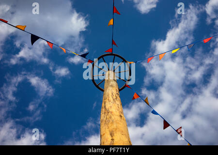 Pole with wagon wheel and colored flags at the fair on the sky background - Stock Image