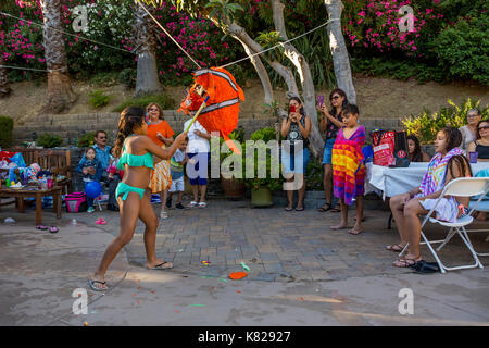 Hispanic girl, hitting a pinata, pinata filled with candy sweets and toys, birthday party, Castro Valley, Alameda County, California, United States - Stock Image