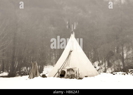 tent of the Indian with snow and fog - Stock Image