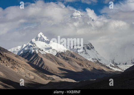 Late afternoon sunlight on Changtse mountain and summit of mount Everest surrounded by clouds - Stock Image