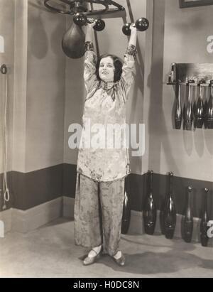 Woman exercising in silk pajamas - Stock Image