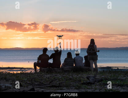 Silhouettes of a group of persons flying a drone at sunset, Loyalty Beach, Seisia, Cape York Peninsula, Far North Queensland, FNQ, QLD, Australia - Stock Image