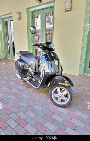 Black Vespa scooter parked on the sidewalk next to a business in Seaside Florida, USA. - Stock Image